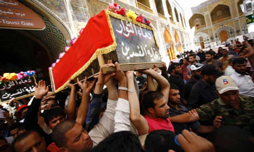 Iraqi men carry the coffins of anti-government protesters on Saturday