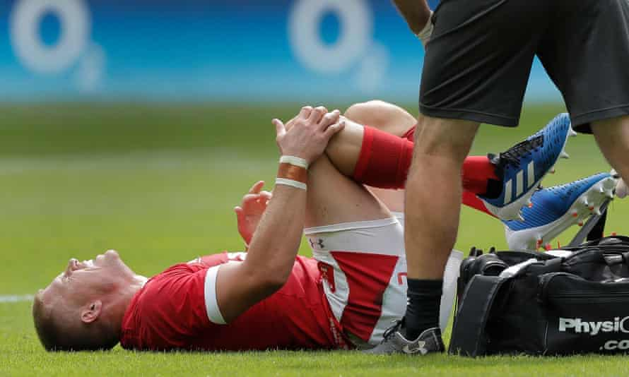 Gareth Anscombe clutches his injured knee before going off.