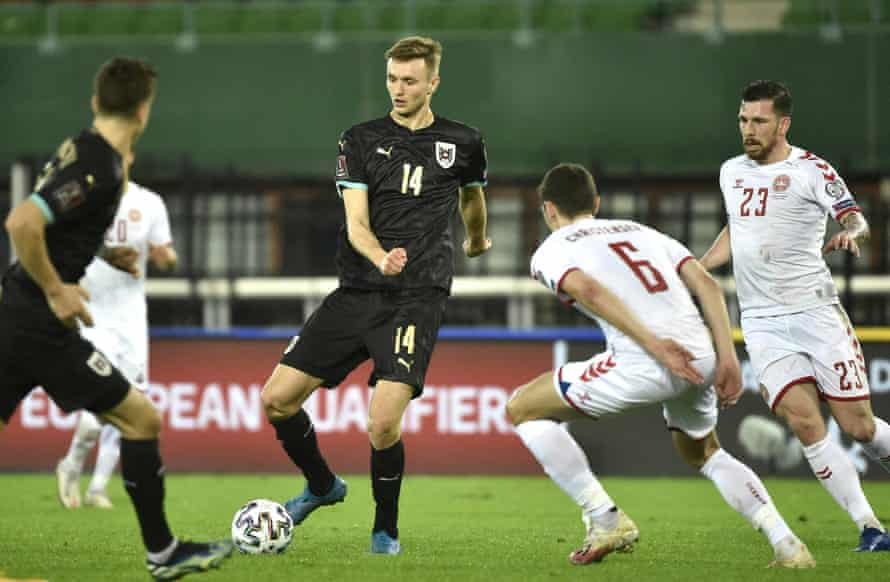 Austria's forward Sasa Kalajdzic (C) passes the ball.