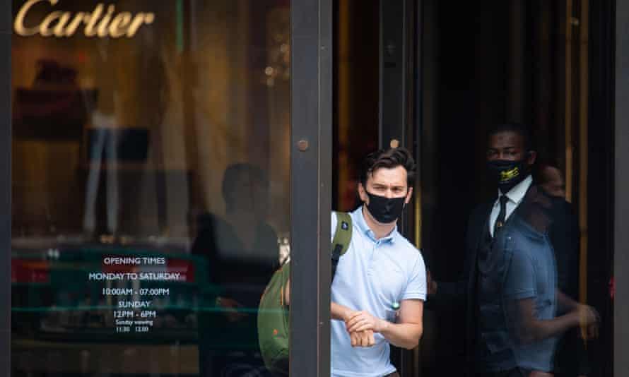A shopper wearing a face covering exits a shop on Regent Street, London