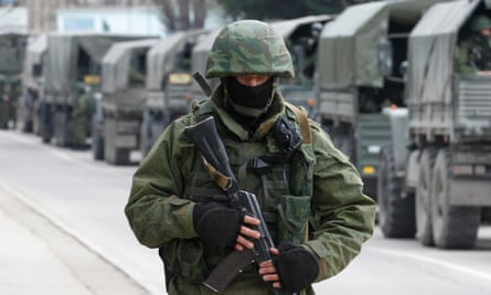 Armed servicemen wait in Russian army vehicles outside a Ukrainian border guard post in the Crimean town of Balaclava in March 2014.