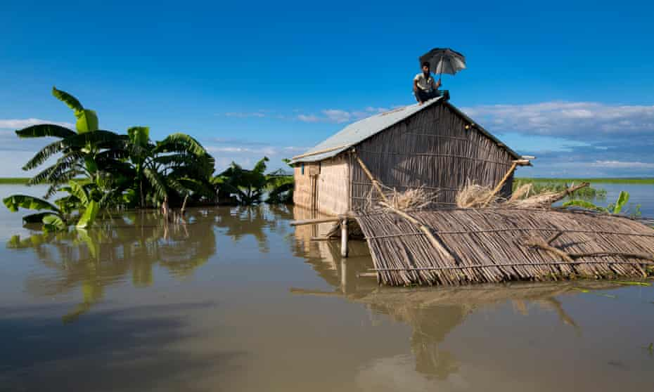 A man sits on the roof of his hut after severe Flooding