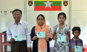 Members of a Rohingya family show their identity cards
