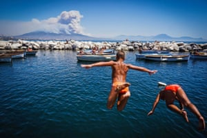 Children jump into the sea as smoke billows from fires around Mount Vesuvius volcano in Naples, Italy