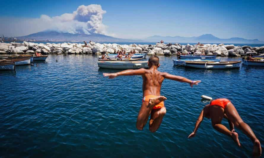 Children jump into the sea as smoke billows from fires around Mount Vesuvius in Naples, Italy