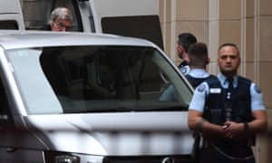 Pell glances up at the cameras as he exits a white van handcuffed and enters the court.