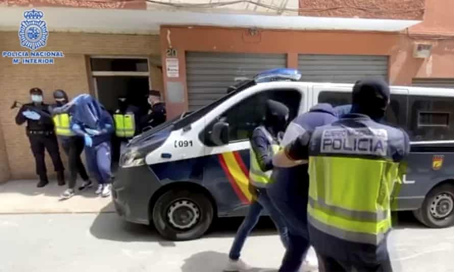 Suspects are led away after the raid in Almeria