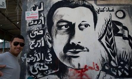 A Palestinian refugee stands next to graffiti depicting assassinated Palestinian writer Ghassan Kanafani, author of novella Return to Haifa.