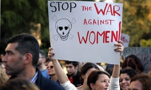 """A woman holds up a sign at a protest saying """"Stop the war against women"""""""