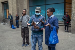 A South African police officer checks the permit of a woman waiting for a minibus taxi to go home