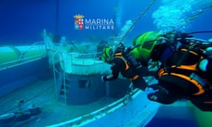 Italian navy divers near the wreck of the fishing boat that sank in the Mediterranean sea last year.