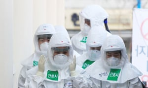 Medical workers in protective gear walk to begin a shift at a hospital in Daegu, South Korea, 23 March 2020.
