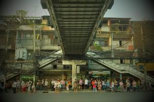 A busy bus stop at rush hour in Bangkok near the central Bangkok footbridge.