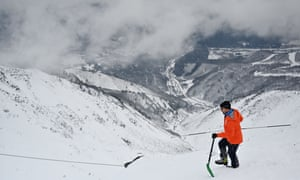 A mountain guide checks snow ahead of a skiing event in Hakuba, western Japan. Some areas have recorded their lowest levels of snow for nearly 60 years.