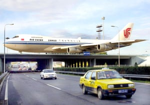 An Air China cargo Boeing 747 jetliner makes its way across a bridge over the highway to the Beijing Capital airport, 3 October 2001.