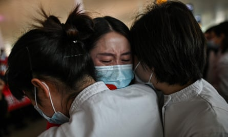 Three women in masks embrace, one facing towards the camera and two away
