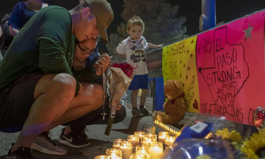 Rene Aguilar and Jackie Flores pray at a makeshift memorial for the victims of Saturday's mass shooting at a shopping complex in El Paso, Texas, 4 August 2019.