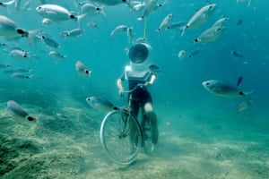 Pula, Croatia A woman dives and pretend to ride a bike at an Underwater Park