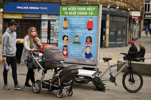 A couple wearing a protective face masks pass a promotion funded by Calderdale Council, an ad bike display advising people on how to slow the spread of the coronavirus, in Halifax in northern England on 9 August, 2020, as local lockdown restrictions are reimposed due to a spike in cases of the novel coronavirus in the town.