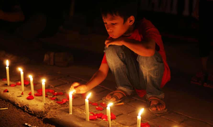 A boy lights candles to show solidarity with the victims of last week's terror attacks in Jakarta, Indonesia.