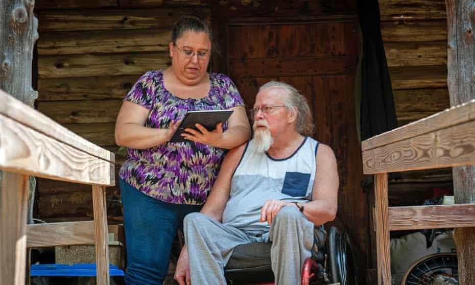 Melissa Harville checks the electronic visit verification app for her partner Kevin Hooper outside their home in Greenbrier, Arkansas.
