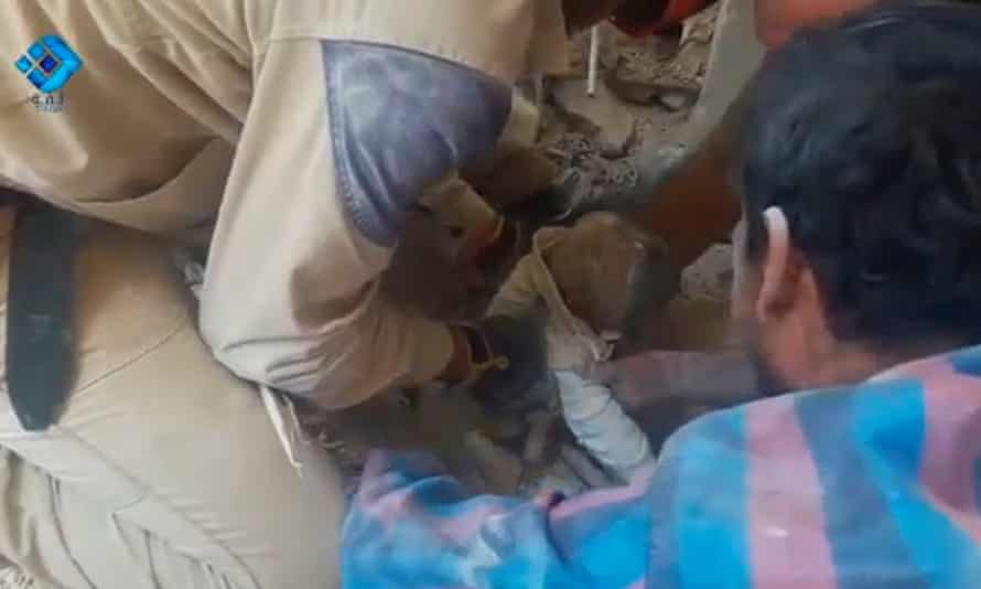 A still image from a video posted on social media shows a baby being rescued from rubble in a collapsed building in Aleppo.