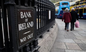 Shoppers pass the Bank of Ireland in Dublin.