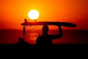 A surfer walks on the beach at sunset West of Los Angeles in California, US