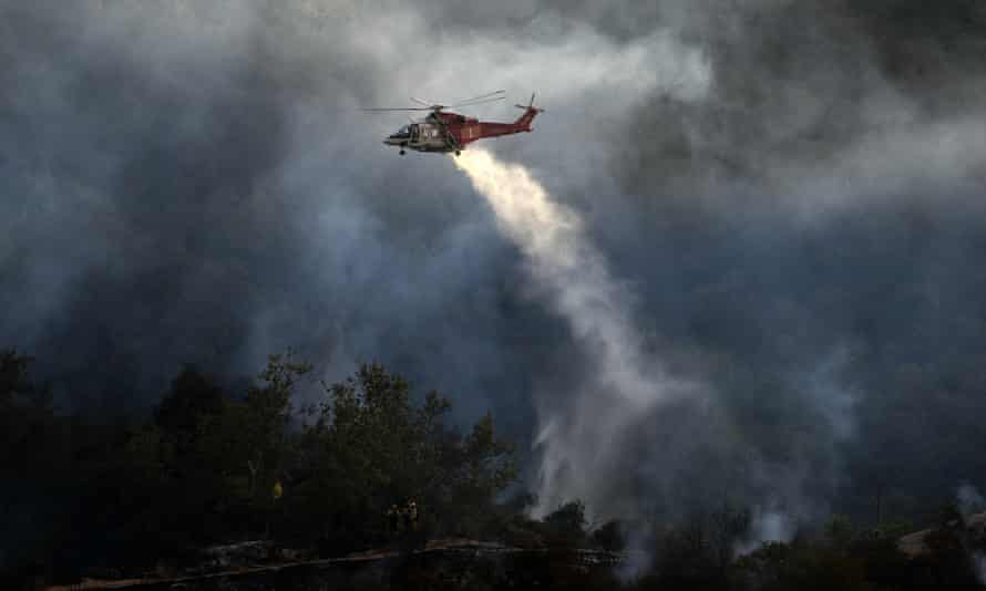 A firefighting helicopter drops water onto a brush fire scorching at least 100 acres in the Pacific Palisades area of Los Angeles.