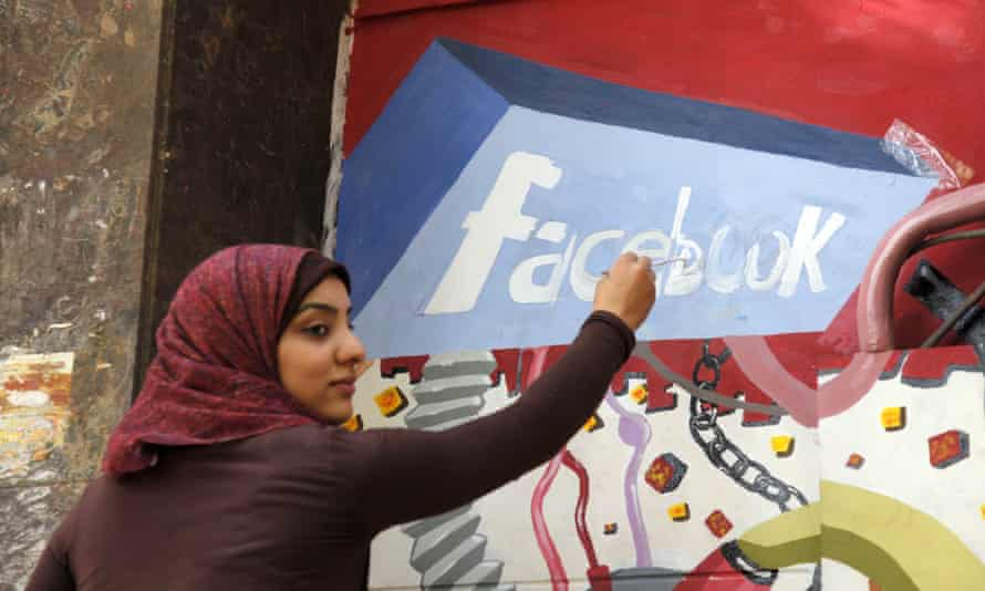 A student from the University of Helwan paints the Facebook logo on a mural in  Cairo, Egypt in 2011.
