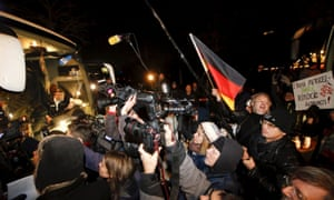 Media and demonstrators stand next to a bus carrying refugees from the Bavarian town of Landshut to Berlin on Thursday.