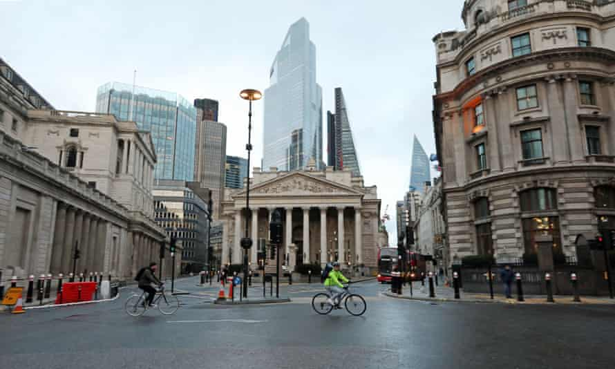 Cyclists pass through an almost-deserted Bank junction in the City of London.