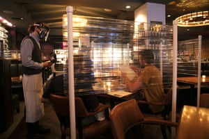 A waiter takes orders from customers surrounded by protective dividers at a seafood restaurant in Los Angeles, United States.