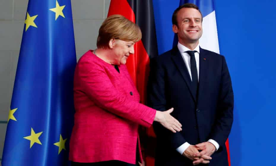 German Chancellor Angela Merkel and French President Emmanuel Macron shake hands after a news conference at the Chancellery in Berlin