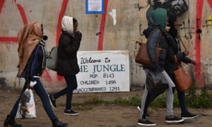 People walk towards an official meeting point as part of the evacuation of the Calais refugee camp.