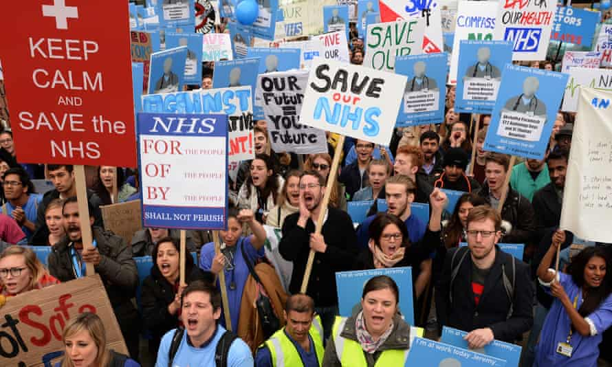 protesters carry placards saying Save The NHS at a protest rally in London