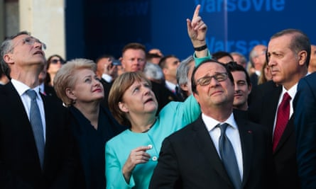 Germany's Chancellor Angela Merkel points at the sky during a fly-past in Warsaw