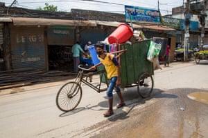 A masked man pushes a waste-laden rickshaw long a street