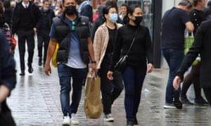 People walk along Oxford Street while wearing face masks.