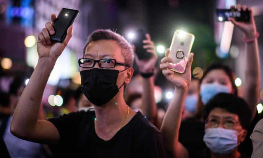 Pro-democracy protesters in Hong Kong hold up their mobile phones