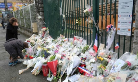 Flowers are laid outside the gendarmerie of Carcassonne where Lt Col Arnaud Beltrame worked.