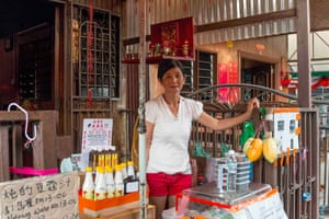 A resident of the Chew Jetty sells snacks to tourists outside her historic stilt home. Her floating village was inundated by tourists after George Town, Malaysia was dubbed a UNESCO World Heritage site in 2008.