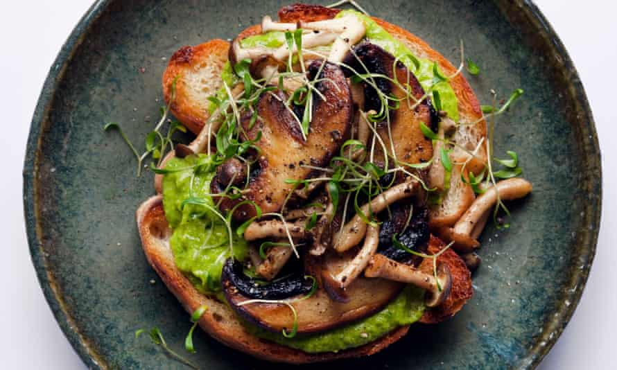 Two slices of toast side by side and piled with mushrooms and sprinkled with little sprouts