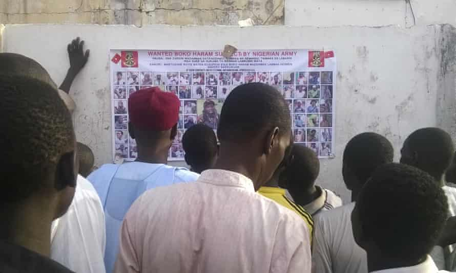 People gather to inspect a wanted poster of Boko Haram suspects in Maiduguri, Nigeria.