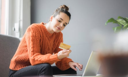 Portrait of content woman sitting on couch using laptop and credit card
