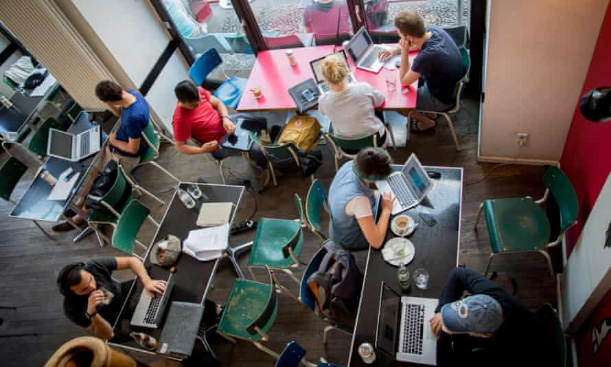 Customers work on their laptops in a Berlin cafe.