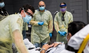 A handout photo made available by the US Navy shows soldiers assigned to Javits New York Medical Station conducting check-in procedures on an incoming Covid-19 patient in New York, New York on 5 April.