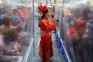 Hanoi, Vietnam: A jewellery shop employee dressed as the God of Wealth encourages people to buy gold for good luck