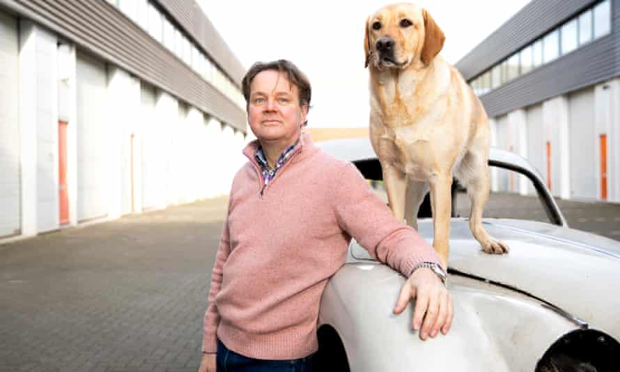 Rolph van Pommeren standing by his car, with his dog standing on top of it