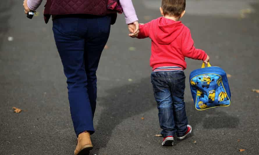 Young boy holds a carer's hand